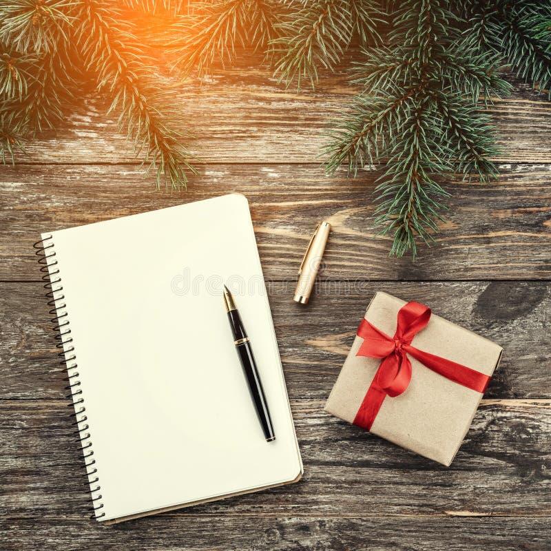 Viejo fondo de madera con las ramas del abeto Cuaderno, regalo Tarjeta de Navidad Visión superior Tarjeta de la enhorabuena con e fotografía de archivo libre de regalías