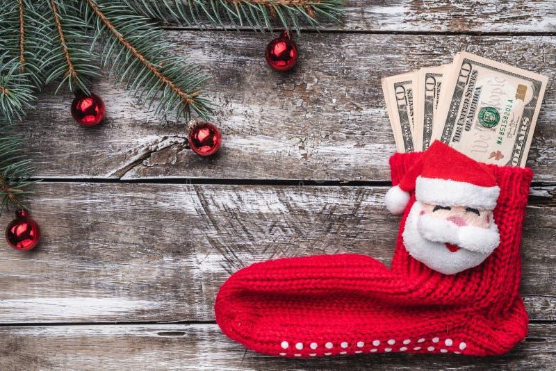 Viejo fondo de madera de la Navidad, una pulsera con un árbol de la chuchería, y el calcetín de Papá Noel con un regalo en la can fotografía de archivo