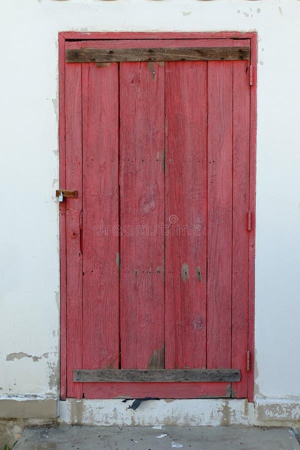Viejo fondo de madera rojo de la puerta con el fondo blanco del muro de cemento de la peladura fotografía de archivo libre de regalías
