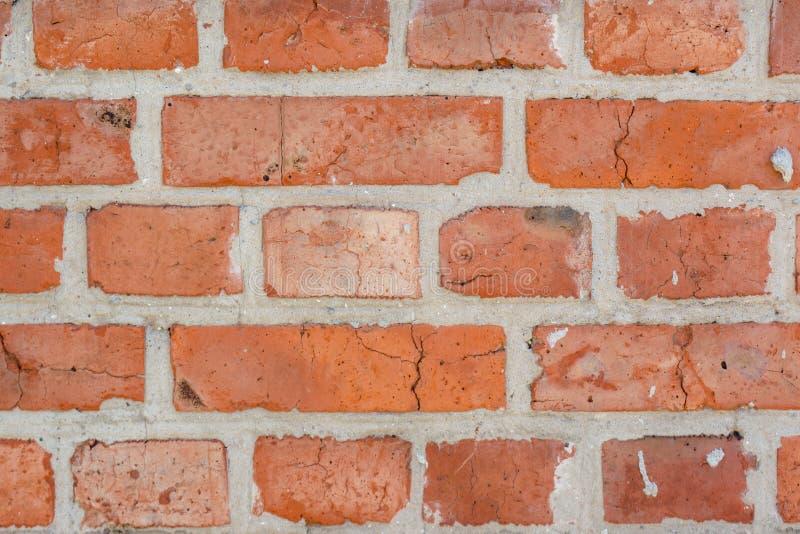 Viejo fondo descolorado rojo de la pared de ladrillos con las grietas y los defectos fotos de archivo