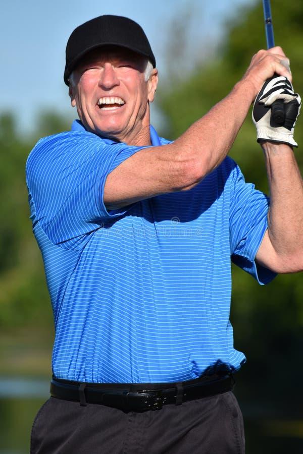 Viejo golfista de sexo masculino mayor que se resuelve con el balanceo de Golf Club fotografía de archivo