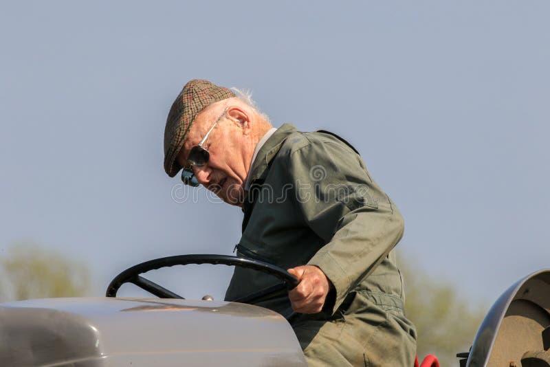 Viejo granjero en el tractor en casquillo en el partido de arado imagenes de archivo