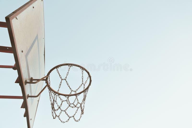 Viejo grunge de cadena oxidado de la cesta del baloncesto con la parte posterior despejada del cielo fotografía de archivo libre de regalías