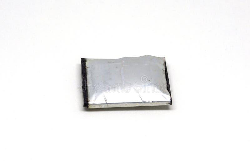 Viejo hinche la batería para el teléfono móvil en un fondo blanco fotos de archivo