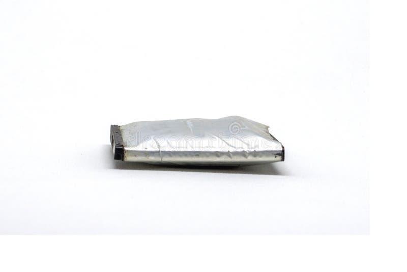 Viejo hinche la batería para el teléfono móvil en un fondo blanco foto de archivo libre de regalías