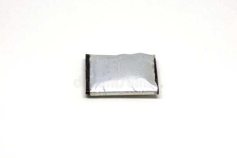 Viejo hinche la batería para el teléfono móvil en un fondo blanco imágenes de archivo libres de regalías