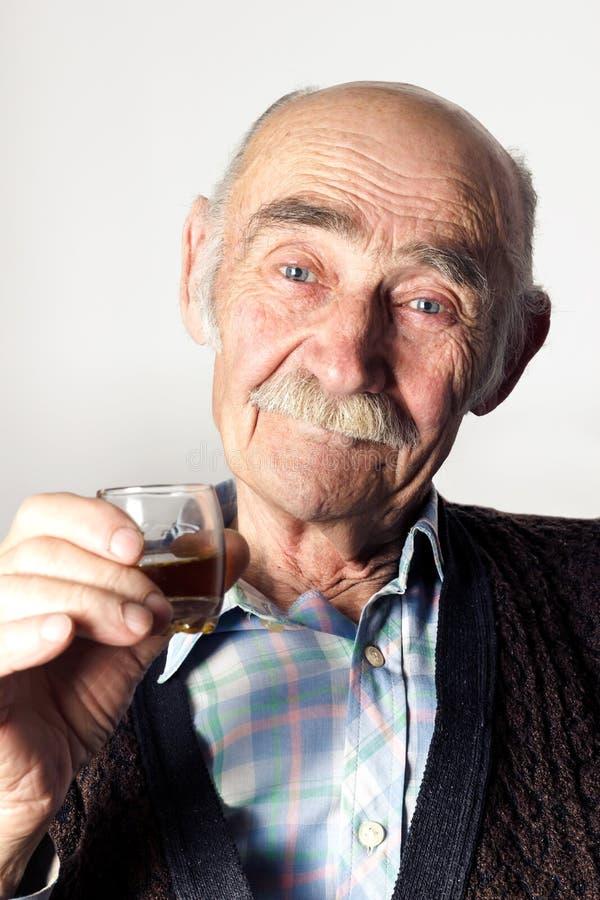 Viejo hombre alegre con los ojos azules que hacen una tostada foto de archivo