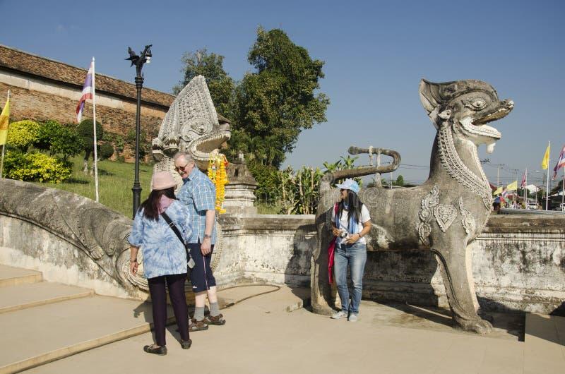 Viejo hombre alemán y mujeres tailandesas que presentan con Singha o el león Guardia fotografía de archivo