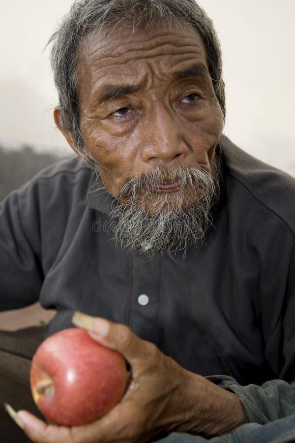 Viejo hombre asiático con la manzana imágenes de archivo libres de regalías
