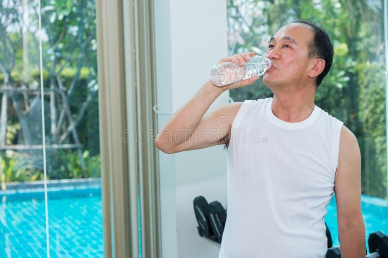 Viejo hombre asiático que coloca y que bebe el agua mineral pura de la botella plástica en el gimnasio después de ejercicio imagen de archivo