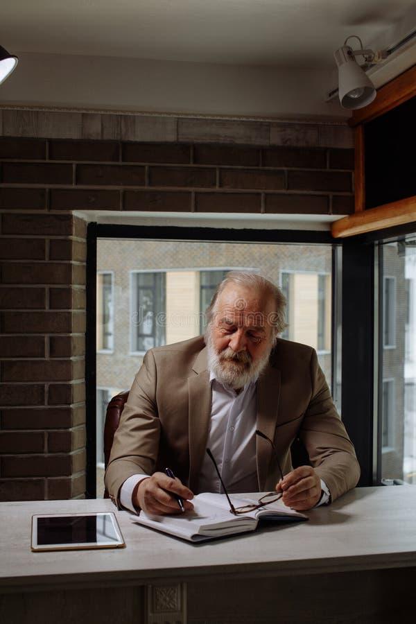 Viejo hombre cansado con los ojos cerrados que se sientan en la tabla en el trabajo en el cuarto oscuro fotos de archivo libres de regalías