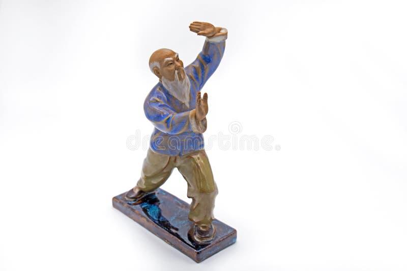 Viejo hombre chino que baila a Tai Chi Statue en el fondo blanco imagen de archivo libre de regalías