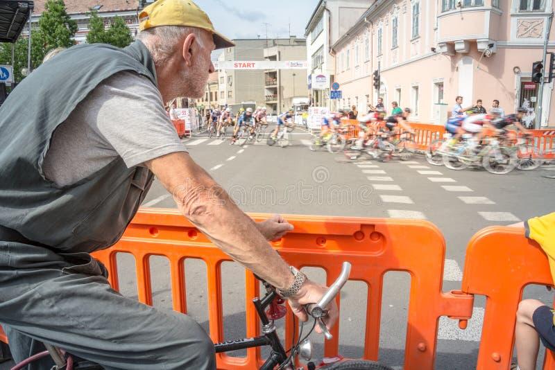 Viejo hombre, ciclista aficionado, observando cyclistes profesionales con su bicicleta de la raza que pasa cerca delante de él co foto de archivo