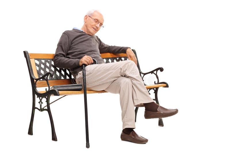 Viejo hombre con el bastón que duerme en un banco de madera fotos de archivo libres de regalías