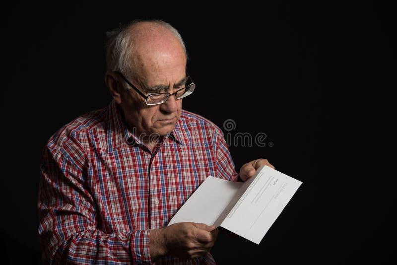 Viejo hombre con el documento del banco imagen de archivo libre de regalías