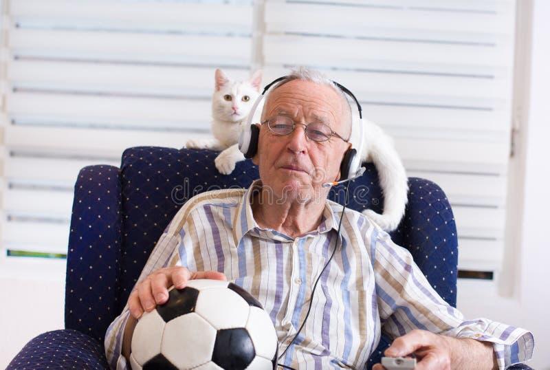 Viejo hombre con el partido de fútbol de observación del gato en la TV imagen de archivo