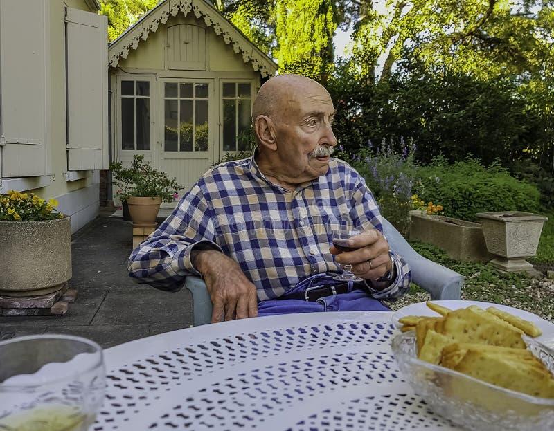 Viejo hombre con un vidrio de la bebida que se sienta en una tabla en el jardín fotos de archivo libres de regalías