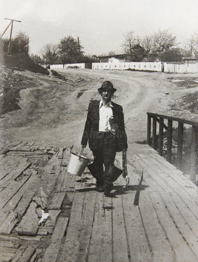 Viejo hombre de la foto del vintage con una caña de pescar imagen de archivo libre de regalías