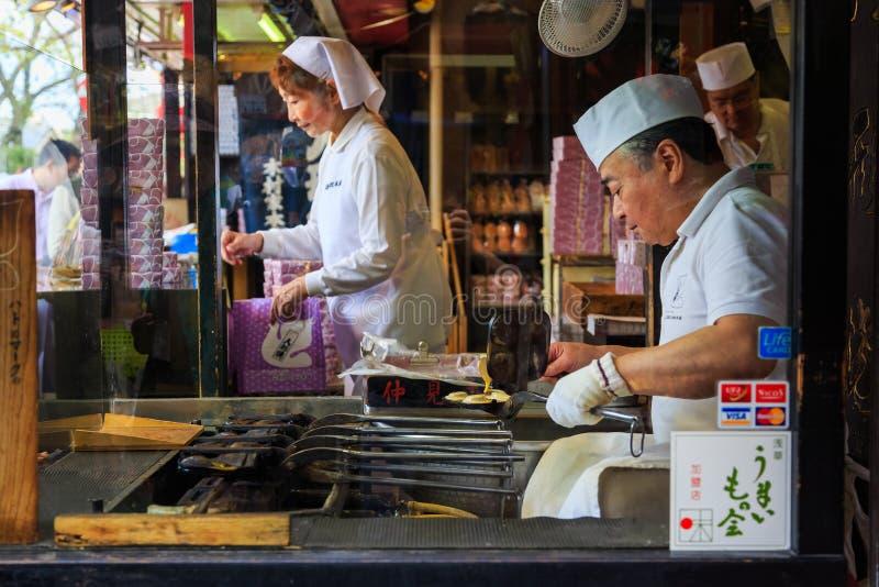 Viejo hombre de la panadería que hace bocado famoso de Nakamise Dori el área que hace compras del templo de Sensoji el templo fam imagen de archivo libre de regalías
