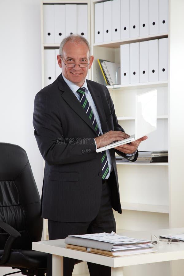 Viejo hombre de negocios con la computadora portátil imagen de archivo libre de regalías