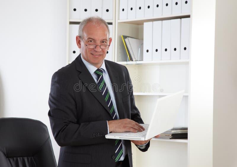 Viejo hombre de negocios con la computadora portátil imagen de archivo