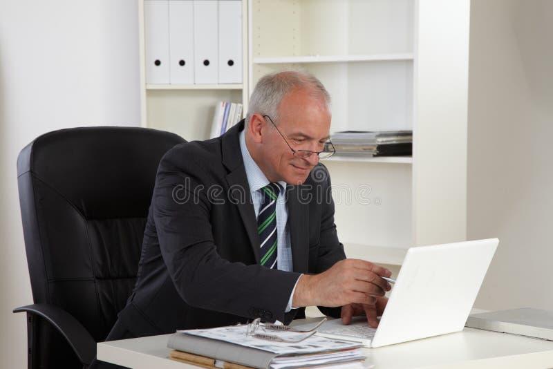Viejo hombre de negocios con la computadora portátil imagenes de archivo