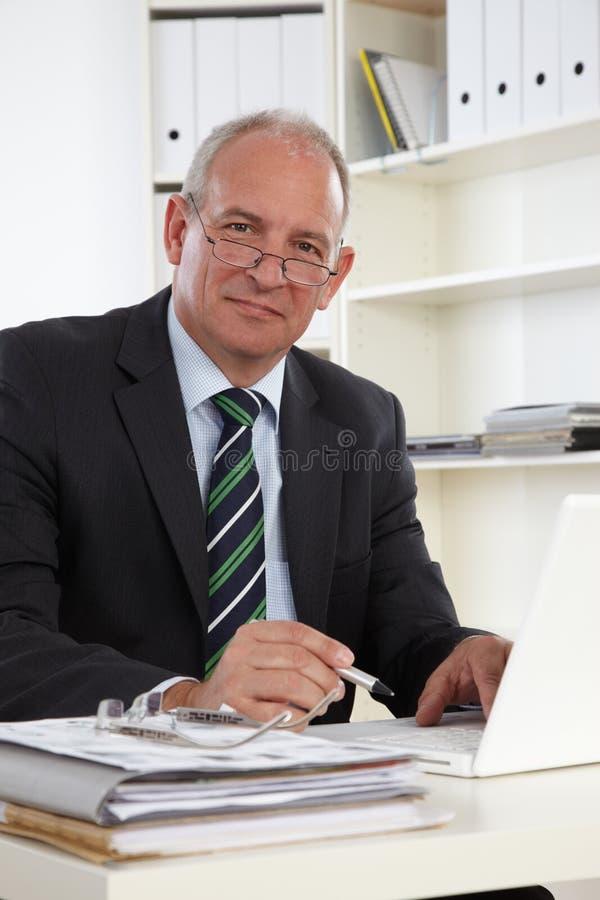 Viejo hombre de negocios con la computadora portátil foto de archivo libre de regalías