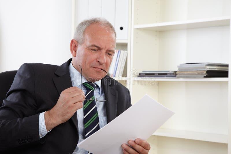 Viejo hombre de negocios en oficina imagen de archivo libre de regalías