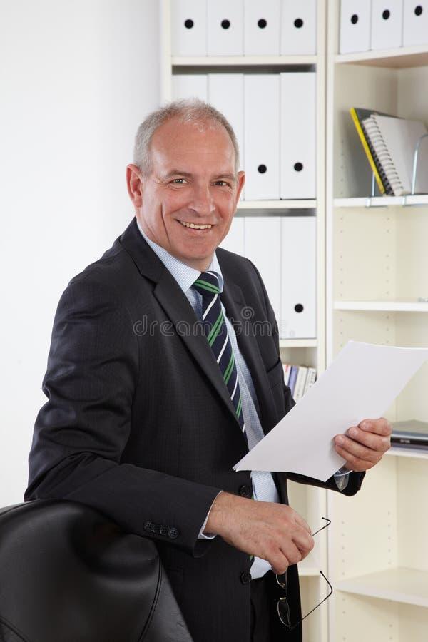 Viejo hombre de negocios en oficina fotografía de archivo libre de regalías