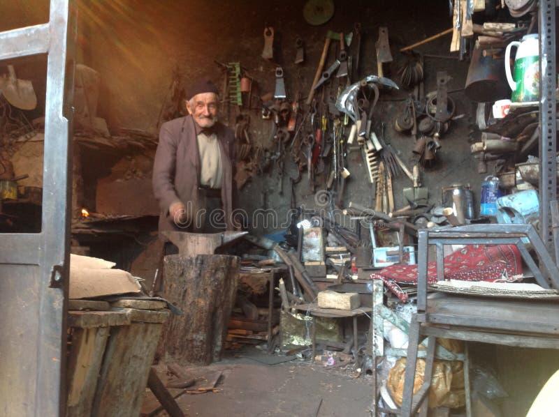 Viejo hombre del artesano que trabaja en su tienda del herrero en Roudbar, Irán foto de archivo libre de regalías