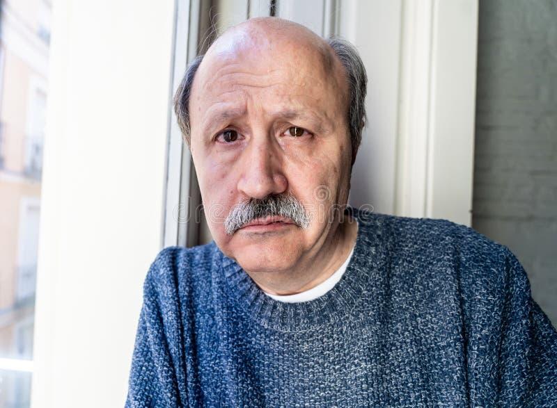Viejo hombre deprimido que mira a través de la ventana que siente sufrimiento solo e infeliz de la depresión foto de archivo