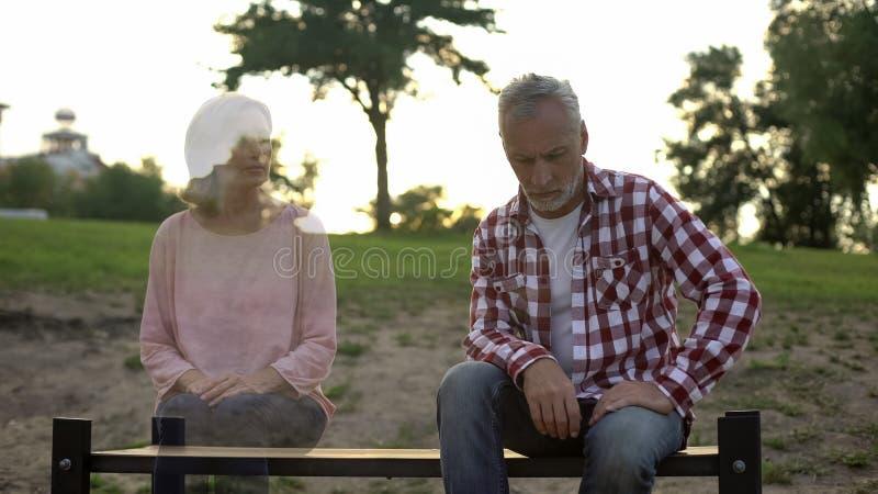 Viejo hombre deprimido que se sienta en banco, esposa que aparece por otra parte, dolor de la pérdida, memorias fotos de archivo