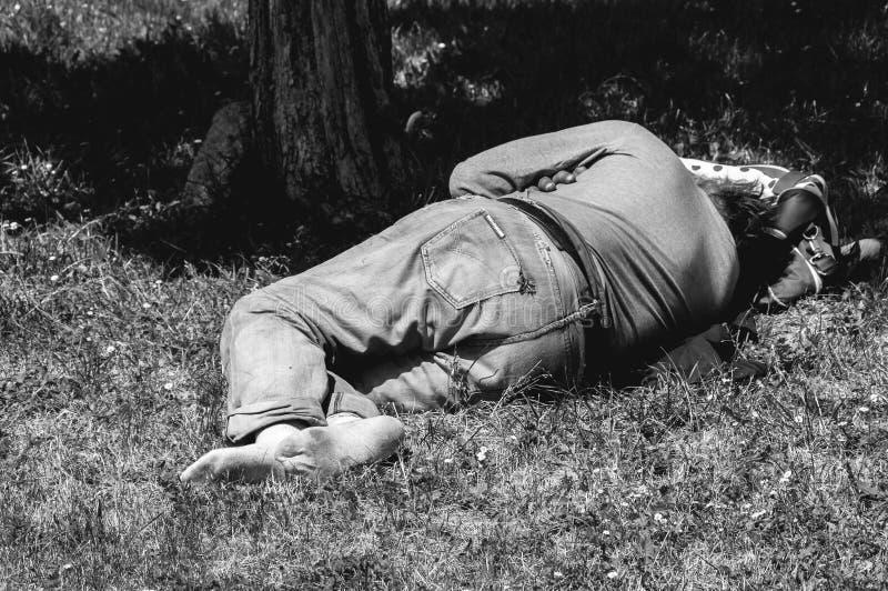 Viejo hombre descalzo de los desamparados o del refugiado que duerme en la hierba en el parque usando su bolso del viaje como alm imagenes de archivo