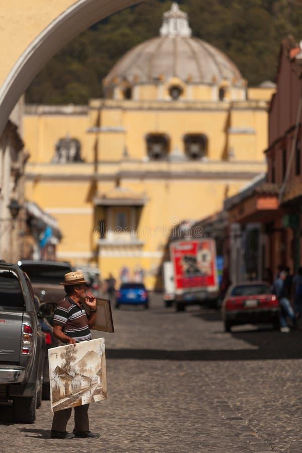 Viejo hombre en Antigua Guatemala que vende pinturas en la calle imagen de archivo libre de regalías