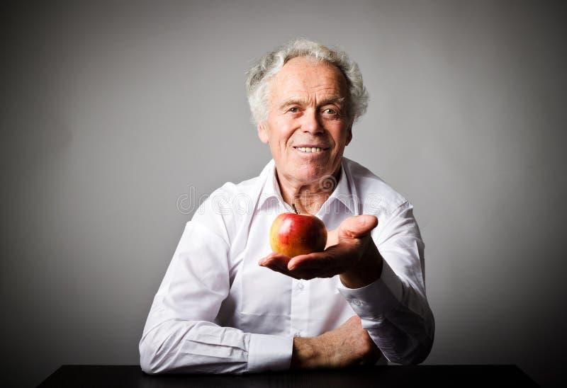 Viejo hombre en blanco y manzana imágenes de archivo libres de regalías