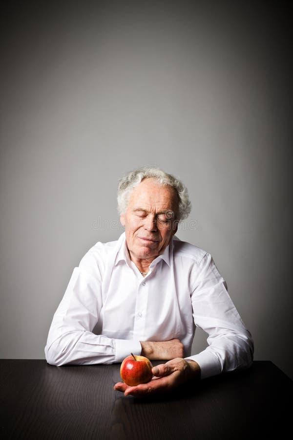 Viejo hombre en blanco y manzana foto de archivo