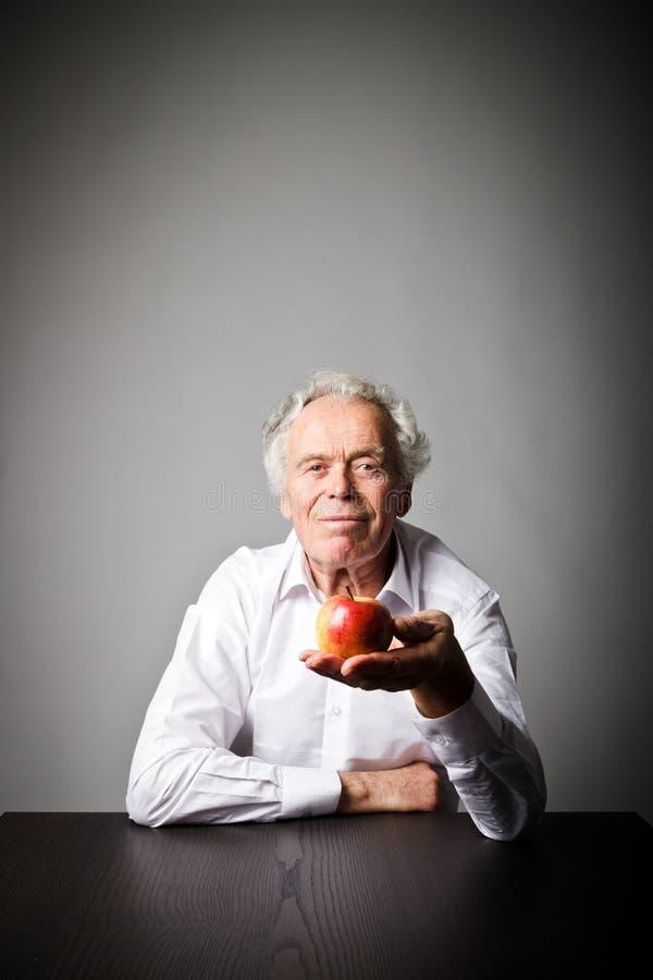 Viejo hombre en blanco y manzana imagenes de archivo