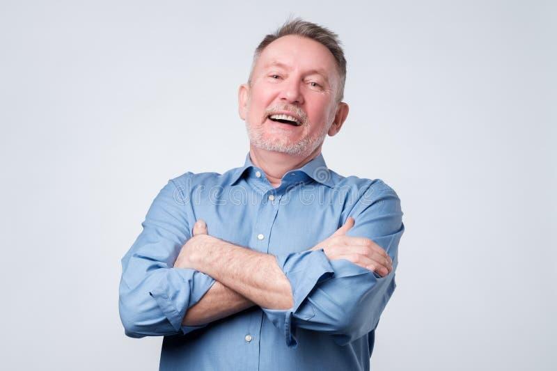 Viejo hombre en brazos plegables, la mirada lejos y la sonrisa de la camisa azul foto de archivo