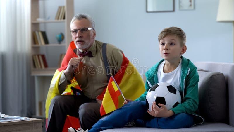 Viejo hombre envuelto en fútbol de observación de la bandera española con el muchacho, preocupándose de juego imagenes de archivo