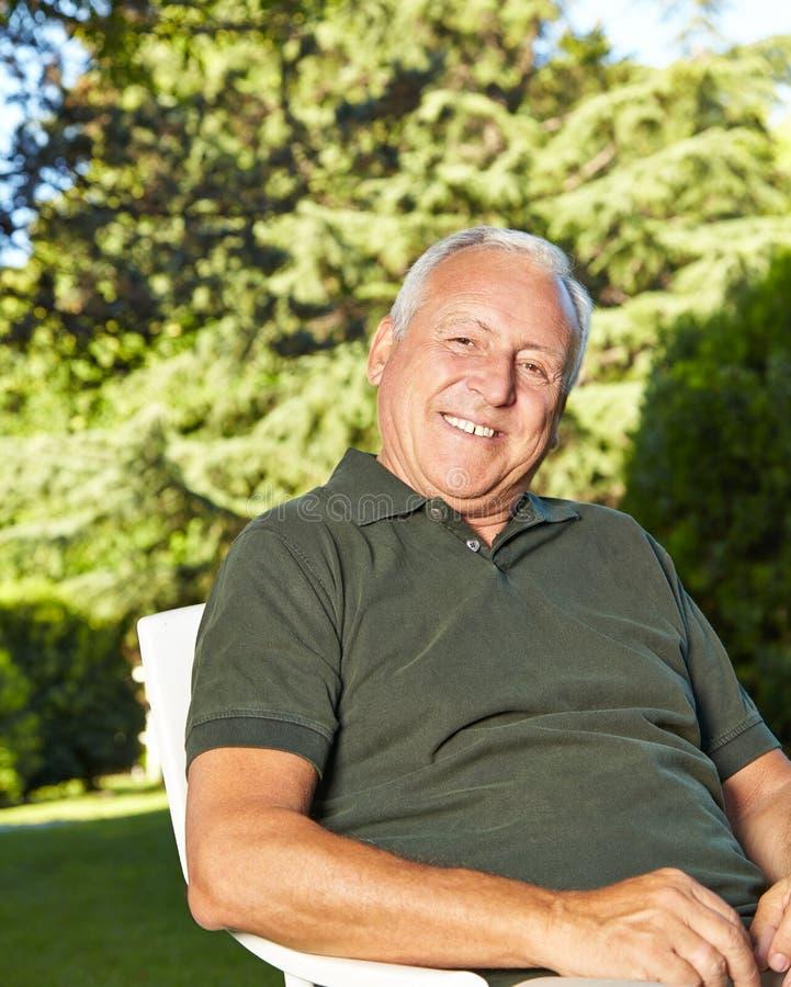 Viejo hombre feliz en un jardín fotografía de archivo