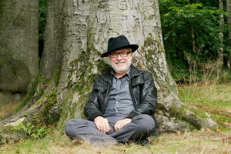 Viejo hombre feliz que se sienta debajo de árbol en el bosque imagenes de archivo