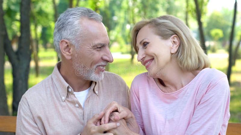 Viejo hombre feliz y mujer que se miran con amor y que llevan a cabo las manos, fecha fotografía de archivo libre de regalías
