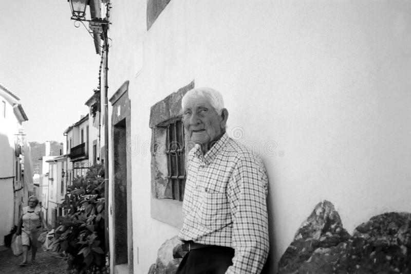 Viejo hombre fuera de su casa En Portugal las personas mayores se sientan a menudo fuera de sus casas como manera de pasar el tie foto de archivo