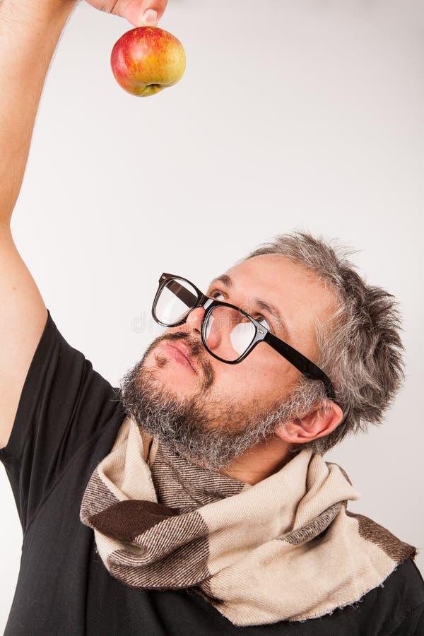 Viejo hombre gruñón con la barba y vidrios grandes del empollón y una manzana imágenes de archivo libres de regalías