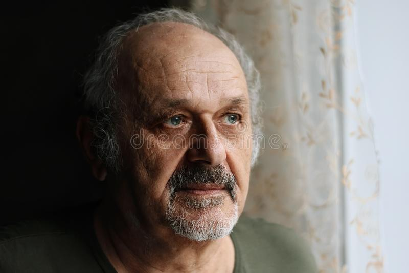 Viejo hombre infeliz dentro: hombre mayor con la situación gris de la barba y del bigote cerca de la ventana Soledad, concepto en fotos de archivo