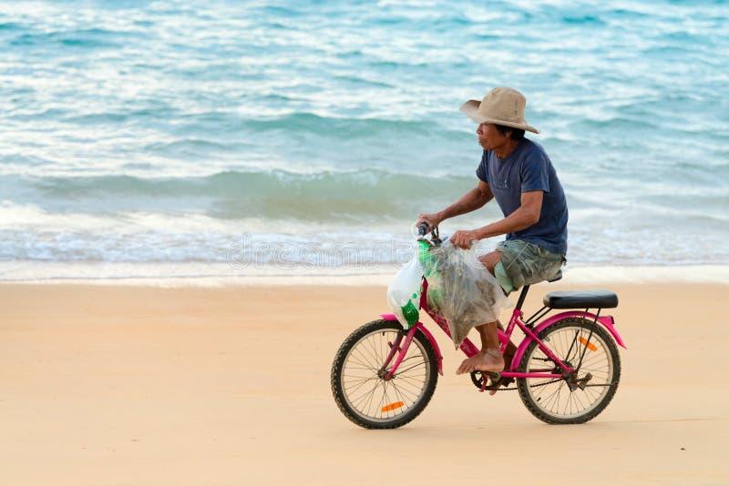 Viejo hombre local nativo que monta en bicicleta a lo largo de una playa, Tailandia imagen de archivo