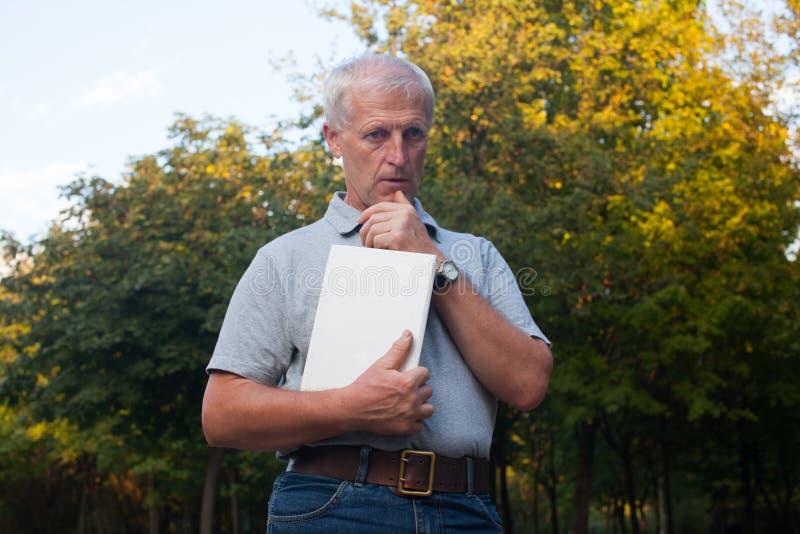 Viejo hombre pensativo con el libro foto de archivo