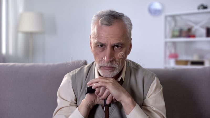 Viejo hombre presionado que se inclina en el palillo, solo y enfermo en la edad avanzada, ayuda social imágenes de archivo libres de regalías