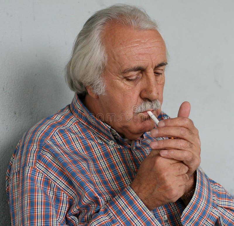 Viejo hombre que aligera un cigarrillo fotos de archivo libres de regalías