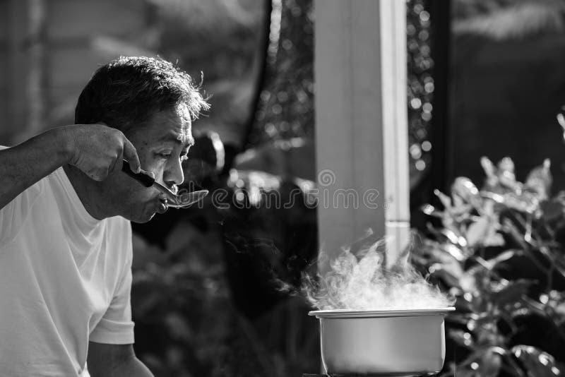 Viejo hombre que cocina la comida de la comida de la mañana en pote caliente en estufa de gas del lpg fotografía de archivo